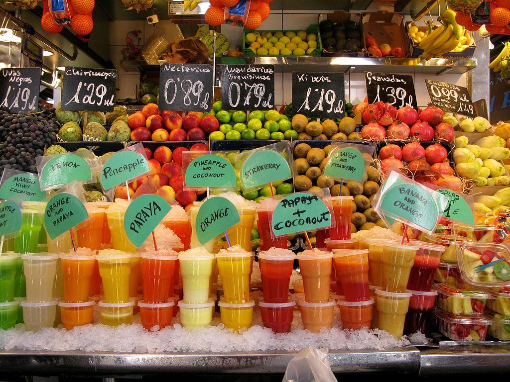 Esposizione di frullati di frutta fresca su un bancone del mercato La Boqueria.