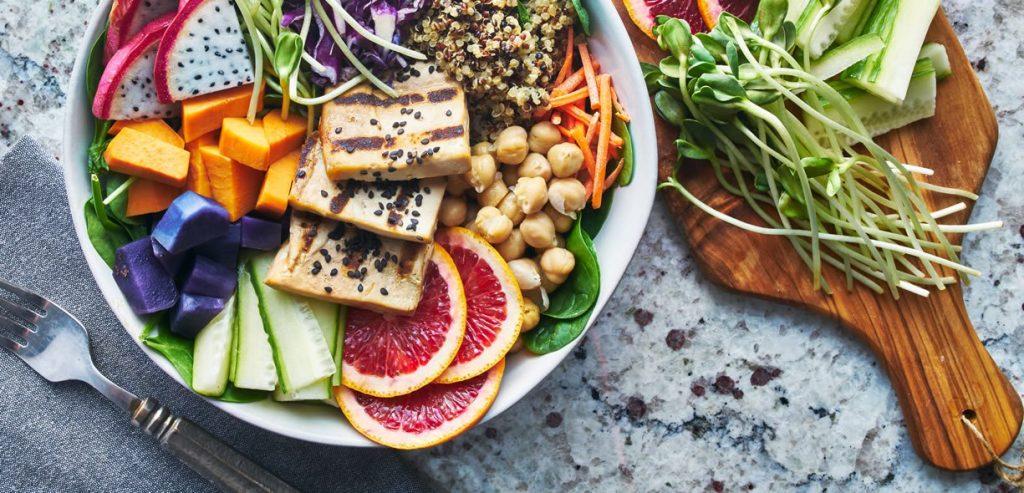 Mangiare vegano. Un piatto ripieno di frutta, tofu e altri alimenti vegani.