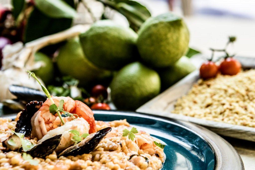La foto vede un primo piatto di riso e cozze e qualche frutto nello sfondo. Una rappresentazione di un piatto del THotel