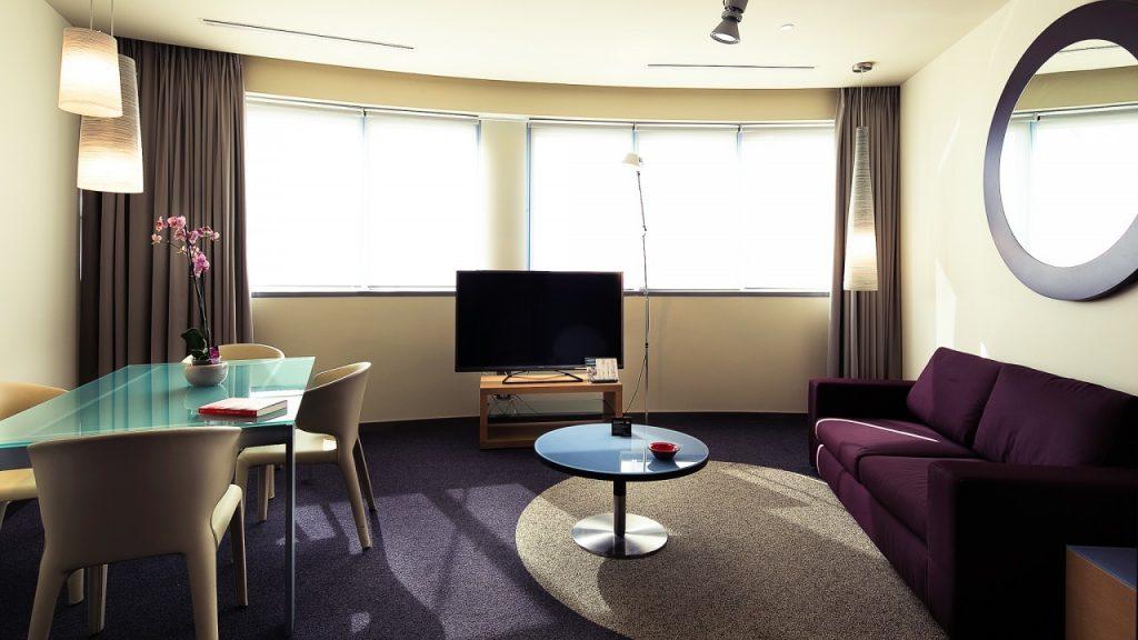 Nella foto si vede l'interno della stanza del THotel Executive Suite. Si vedono le finestre, il divano e il tavolo.