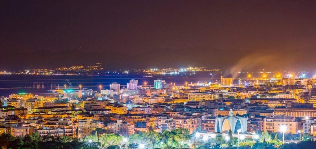 Una nuova Piazza: Pratzita – Piazzetta Società Rari Nantes. La foto ritrae uno scorcio panoramico della città di Cagliari di notte, tutta illuminata.