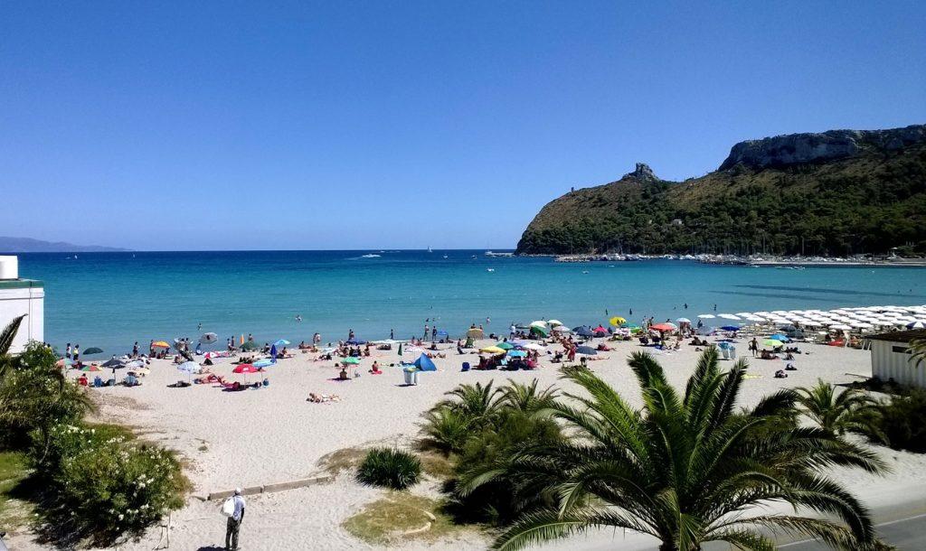Tempo di mare e le spiagge di Cagliari e dintorni. La Spiaggia Del Poetto. In questa foto vediamo un panorama della spiaggia con alcuni bagnanti e sullo sfondo la Sella del Diavolo