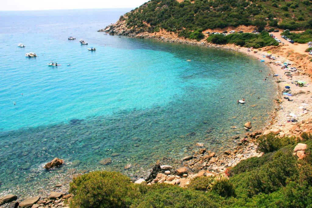 Tempo di mare e le spiagge di Cagliari e dintorni.  La Spiaggia di Cala Regina. La foto prende una parte della spiaggia con in lontananza alcune barche.