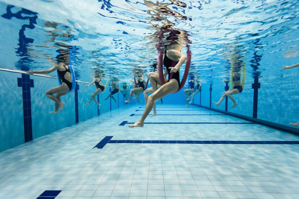 Lo Sport alla cagliaritana: Il Nuoto. Dove praticarlo? La foto vede il fondale della piscina Acquasport in cui alcune utenti fanno esercizi di ginnastica in acqua con degli attrezzi