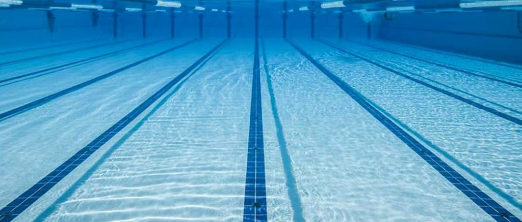 Lo Sport alla cagliaritana: Il Nuoto. Dove praticarlo?. Si vede il fondo di una piscina con le righe che segnalano le corsie