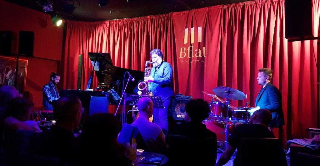 Bflat il cuore della musica Jazz di Cagliari. Concerto con il sax di Emanuele Cisi che si vede in primo piano, insieme alla sua band di musicisti.