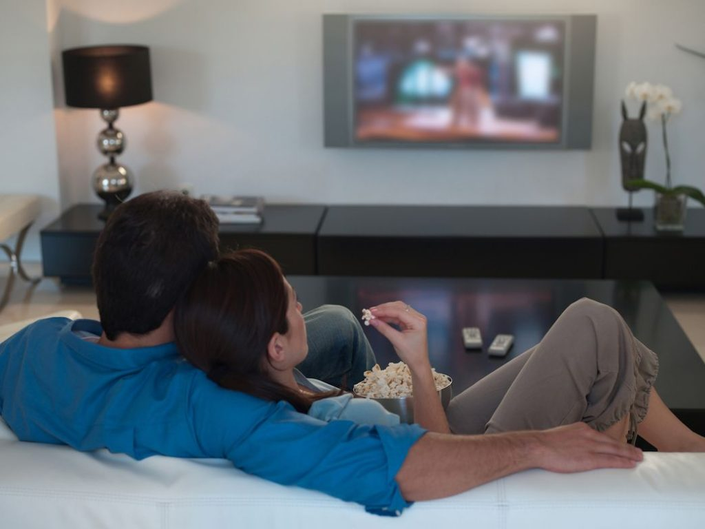 Digitale terrestre 2021 si cambia (Ancora). Coppia Davanti Tv. Una coppia (uomo e donna) seduti sul divano mentre guardano la televisione.