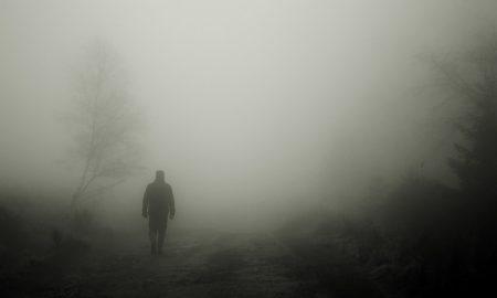 Mommotti - Un uomo vestito di nero che vaga nella nebbia
