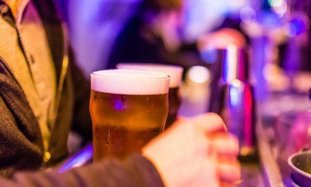 Uomo al bancone del bar con due bicchieri di birra artigianale