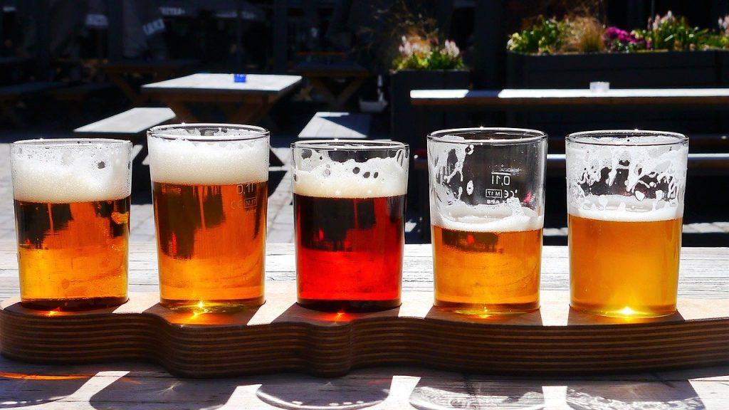Cinque varietà di birre artigianali servite in bicchieri di vetro trasparenti su un tavolo in legno