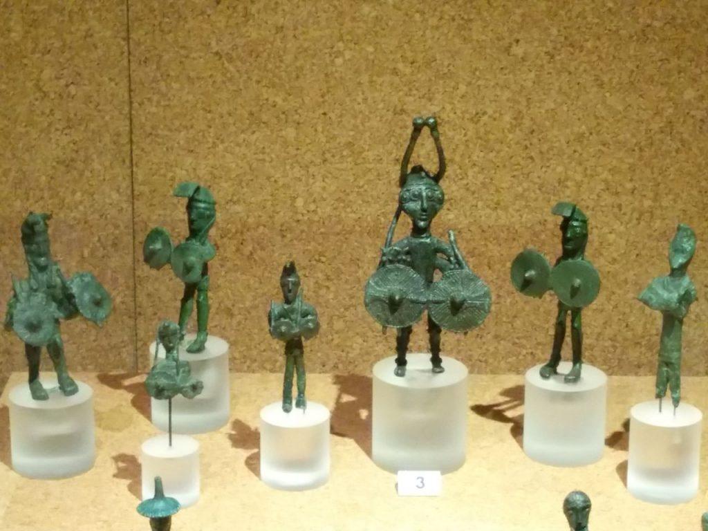 vetrina del Museo archeologico di Cagliari che contiene bronzetti nuragici esposti su piccoli piedistalli di vetro