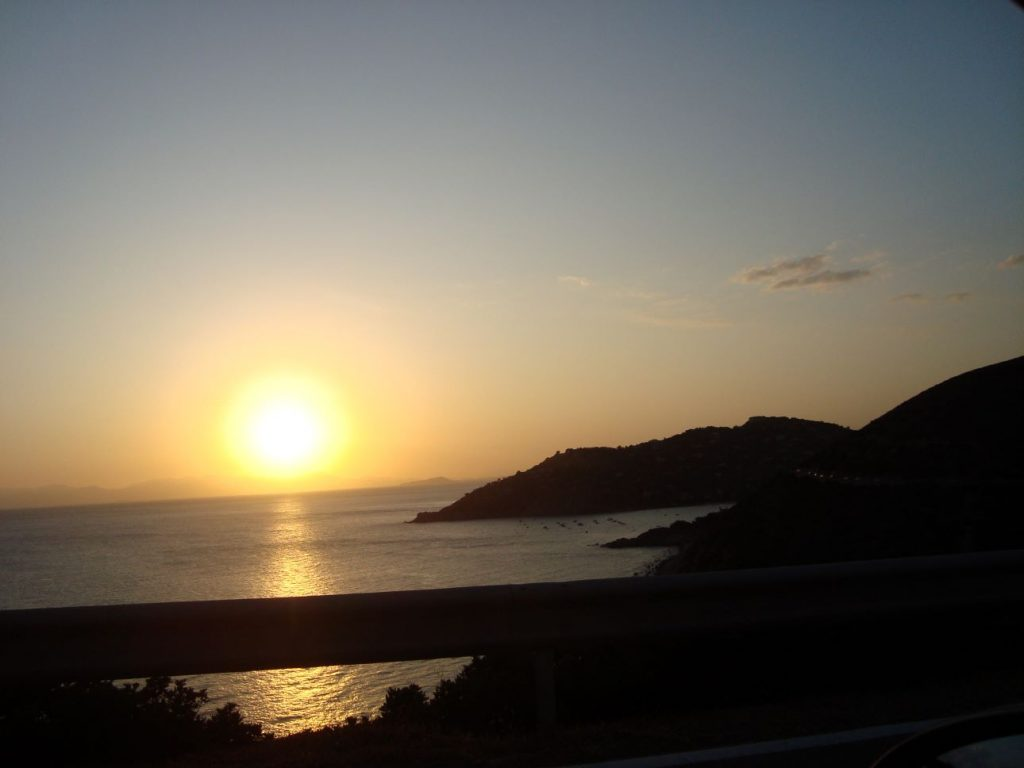 panorama sul mare della sardegna con un grande disco solare all'orizzonte_ sa mama e su sole