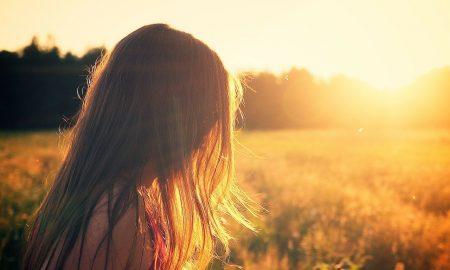 bambina con i capelli unghi di spalle che guarda il sole in un campo_Sa Mama e Su Sole