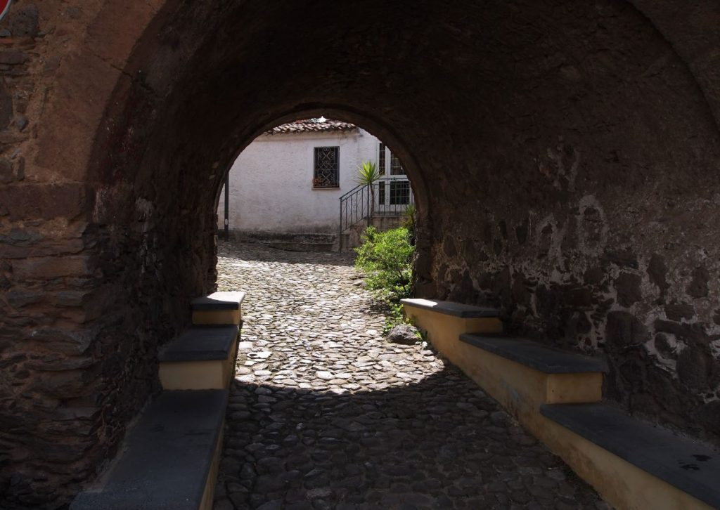 Portico in pietra di un antico paese della sardegna, parte all'ombra e parte al sole con sa Mama e Su Sole
