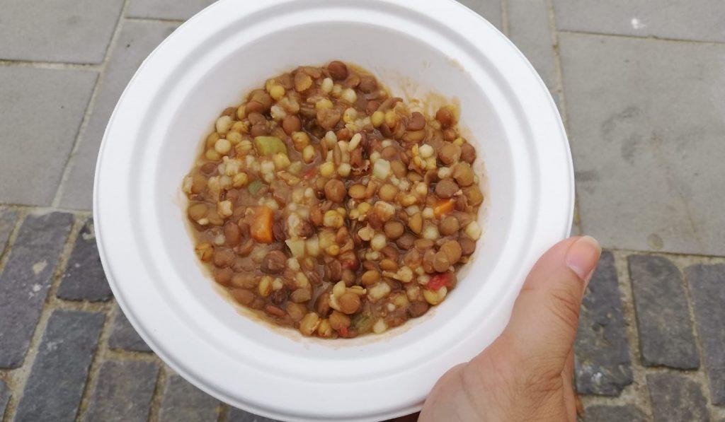 Mano che tiene un piatto bianco che contiene una zuppa di lenticchie, cibo delle Blue Zones