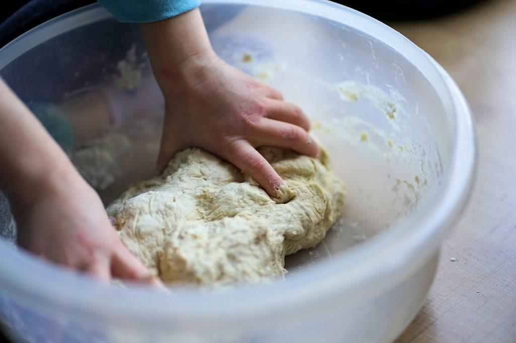 bambino che affonda le mani in un contenitore trasparente con dell'impasto per fare la pasta fresca