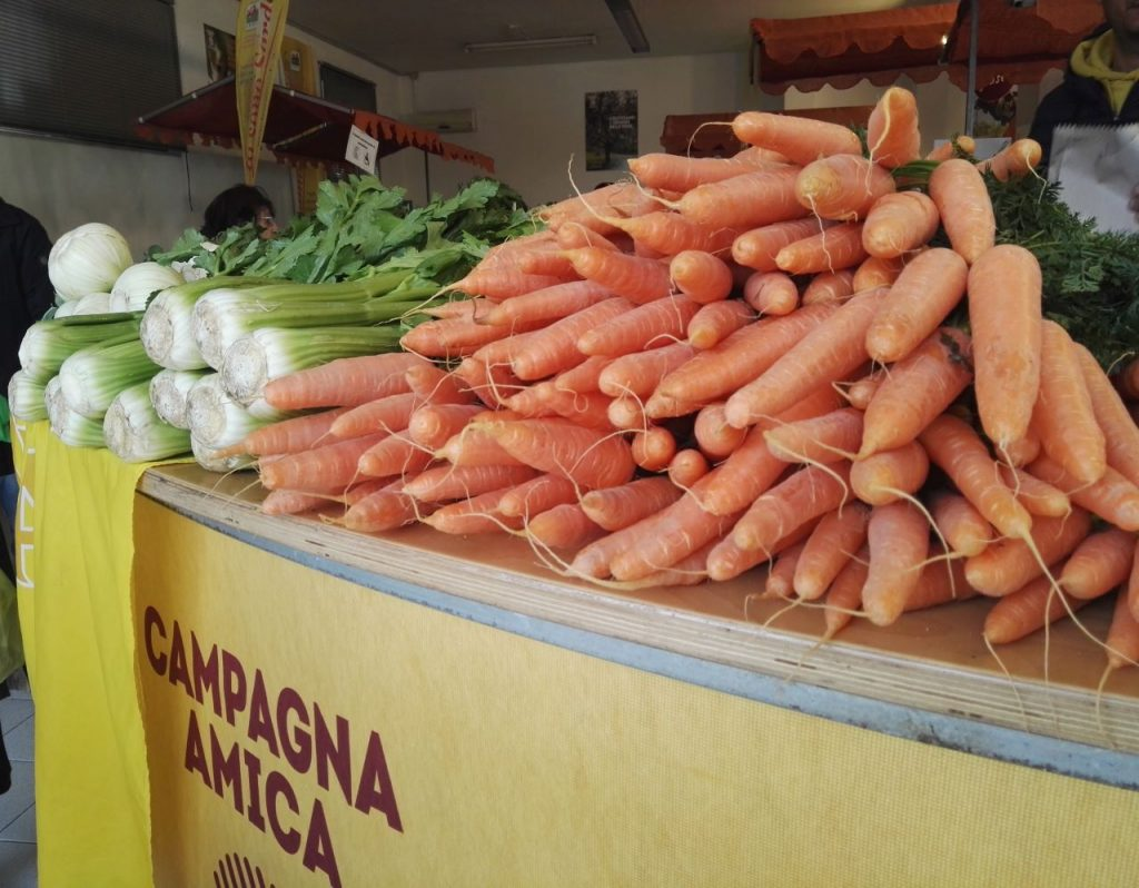 bancone del mercato con mazzi di carote e sedani in primo piano_ coronavirus come fare la spesa