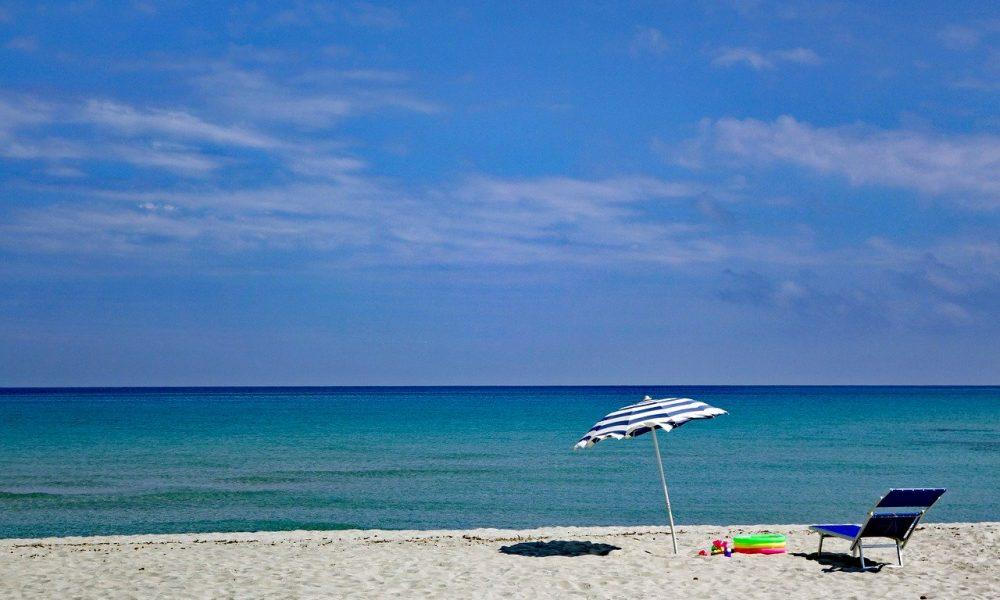 Spiaggia deserta con ombrellone sdraio e sullo sfondo mare e cielo azzurro