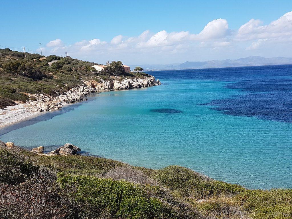 Porzione di costa rocciosa e acque azzurre della spiaggia Di Maladroxia Sant'antioco