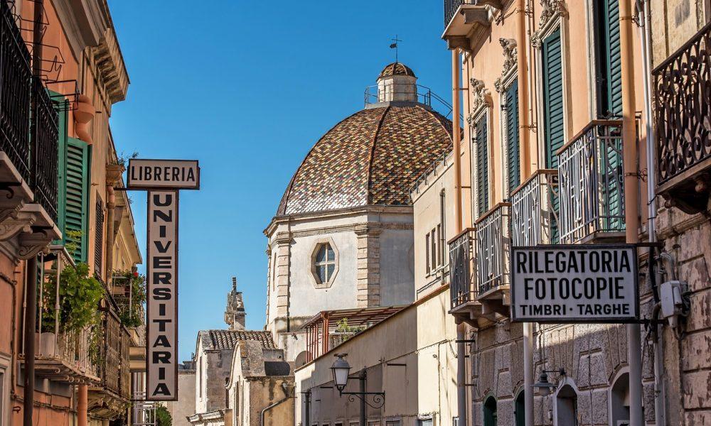 dettaglio di una via della citta di Cagliari, con insegne in primo piano e chiesa sullo sfondo descritta nella guoda del Canonico Spano