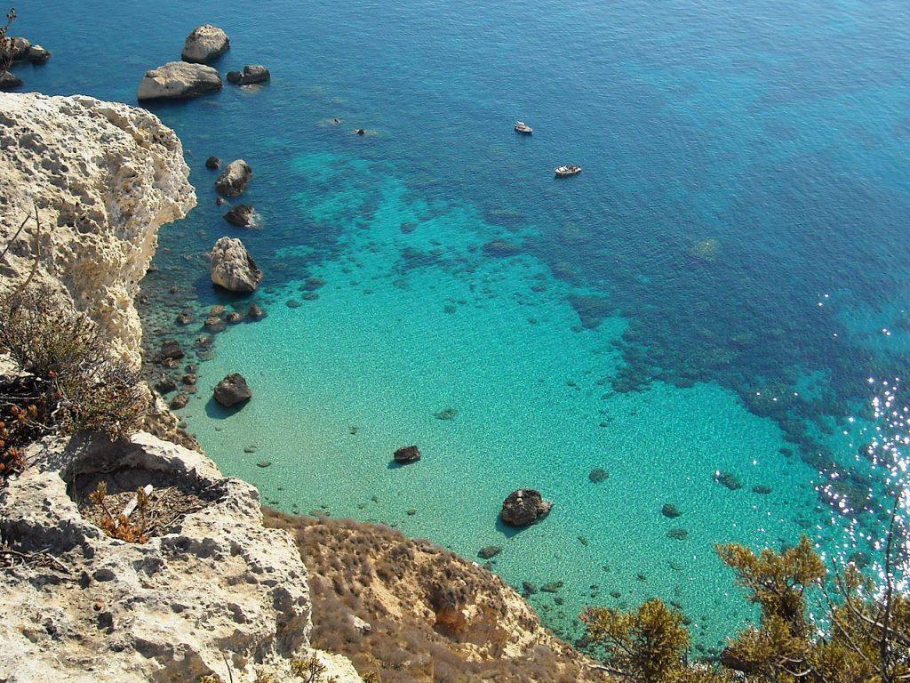 Dettagli di una scogliera del Capo Sant'Elia che arriva fino al mare tra acque cristalline