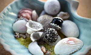 porta oggetti azzurro a forma di conchiglia che contiene amuleti e gioielli sardi