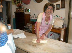 Albertina Piras la donna in primo piano impasta su un taovlo di legno e prepara i dolci di saba