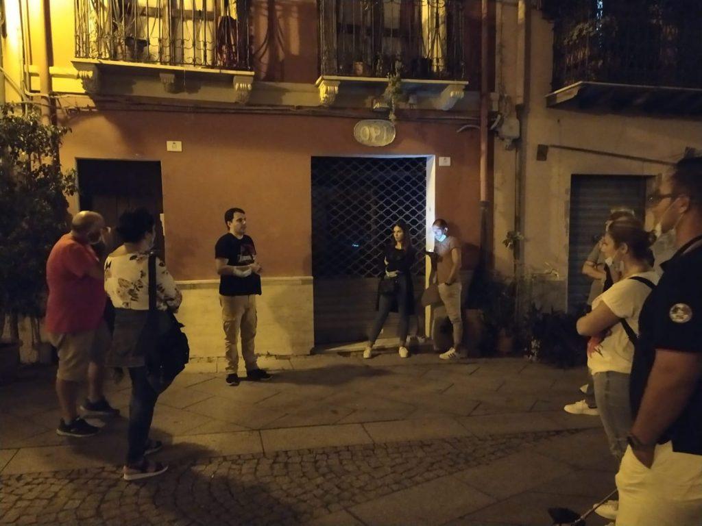 una guida la centro di un gruppo illustr ala facciata di un edificio storico Cagliari Dei Misteri2