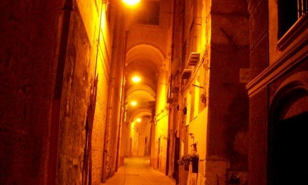una via cittadina durante la notte appena illuminata dai lampioni Cagliari Dei Misteri