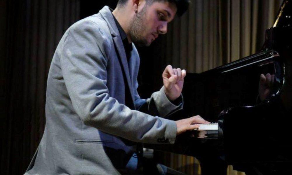 Alessio Zucca, uomo seduto in abito grigio che suona davanti al piano