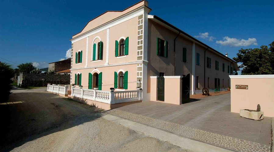primo piano di un edificio rosa con persiane verdi Mondo X Sardegna (1)