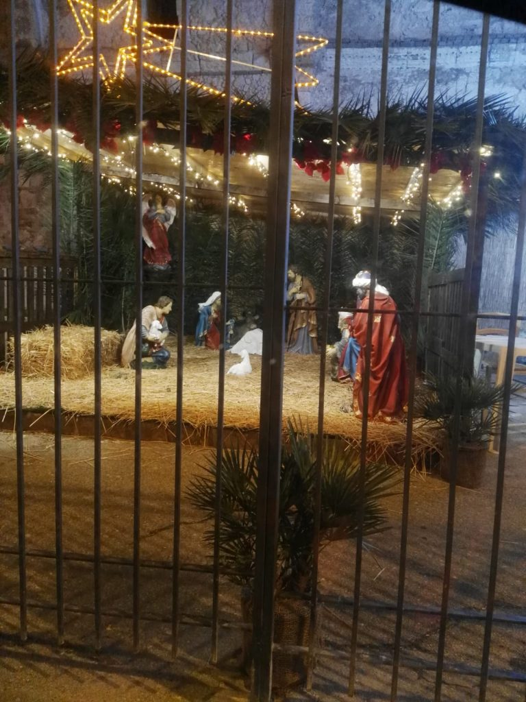 dietro dei cancelli inferro si intravede una capanna con le statue del presepe per il natale nel rione Marina