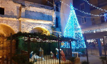 scorcio di una chiesa che accoglie un oresepe e un albero di luci dietro una cancellata per il natale nel rione Marina