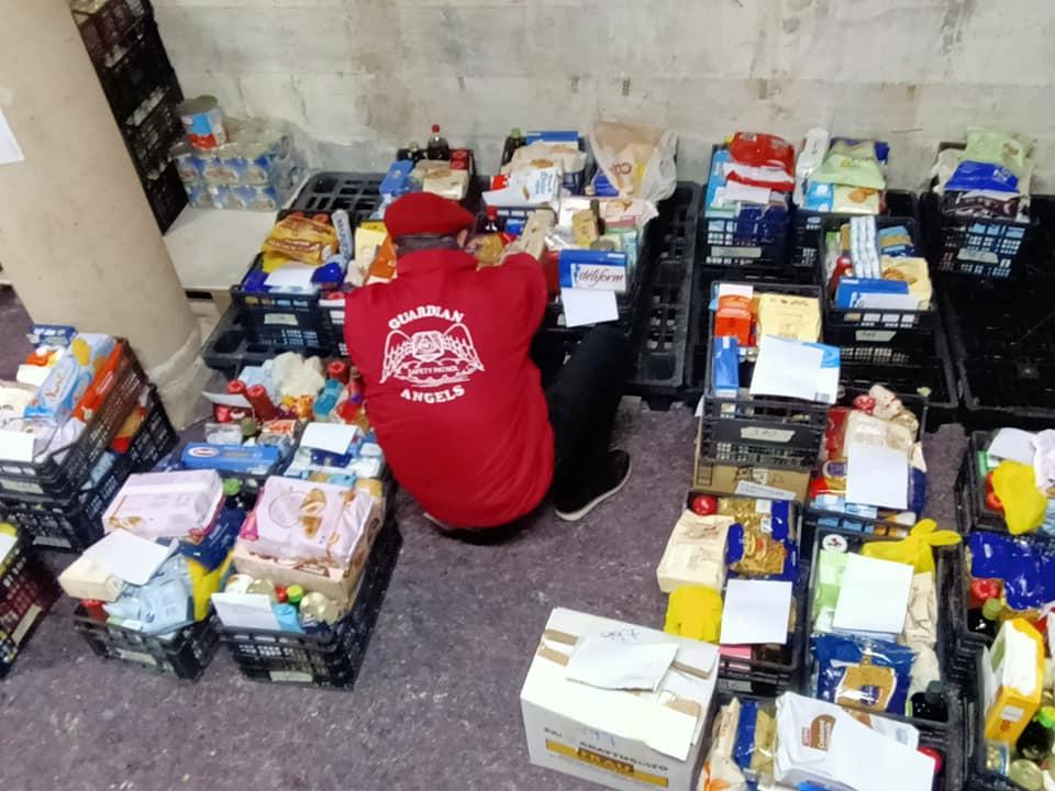 un uomo inchinato conn la felpa rossa è inchinato davanti a cassette di prodotto di prima necessità Spesa Solidale Olbia Miracolo di Natale