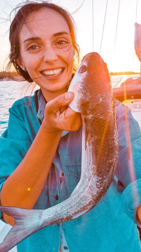 Marta Magnano la ragazza tiene in mano un grosso pesce appena pescato