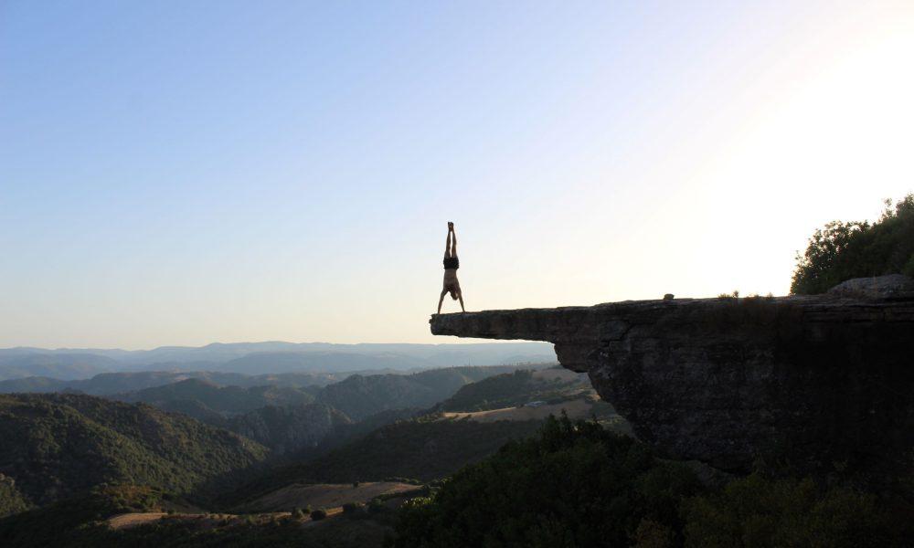 Matteo Sessini, ragazzo in verticale su una roccia panoramica sullo sfondo i monti