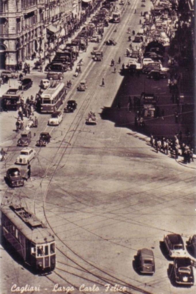 foto in bianco e nero di Cagliari con il tram che corre sulla carreggiata asiseme a auto su Largo Carlo Felice