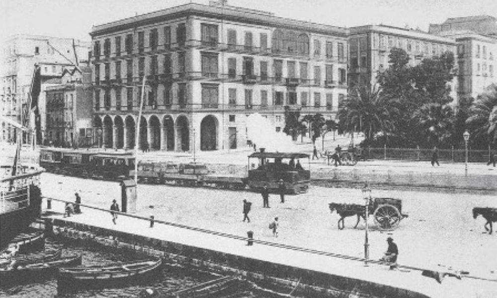 foto d'epoca con treno a vapore in primo piano sullo sfondo il centro storico di cagliari A Bordo Del Tram Cagliari