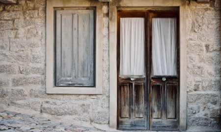una porta e una finestra di legno in una casa antica di granito Diccius Sardi