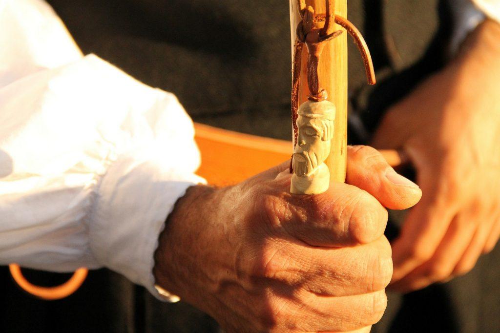 un dettaglio di una mano di un omo vesto in abito tradizionale chi impugna un bastone Diccius Sardi