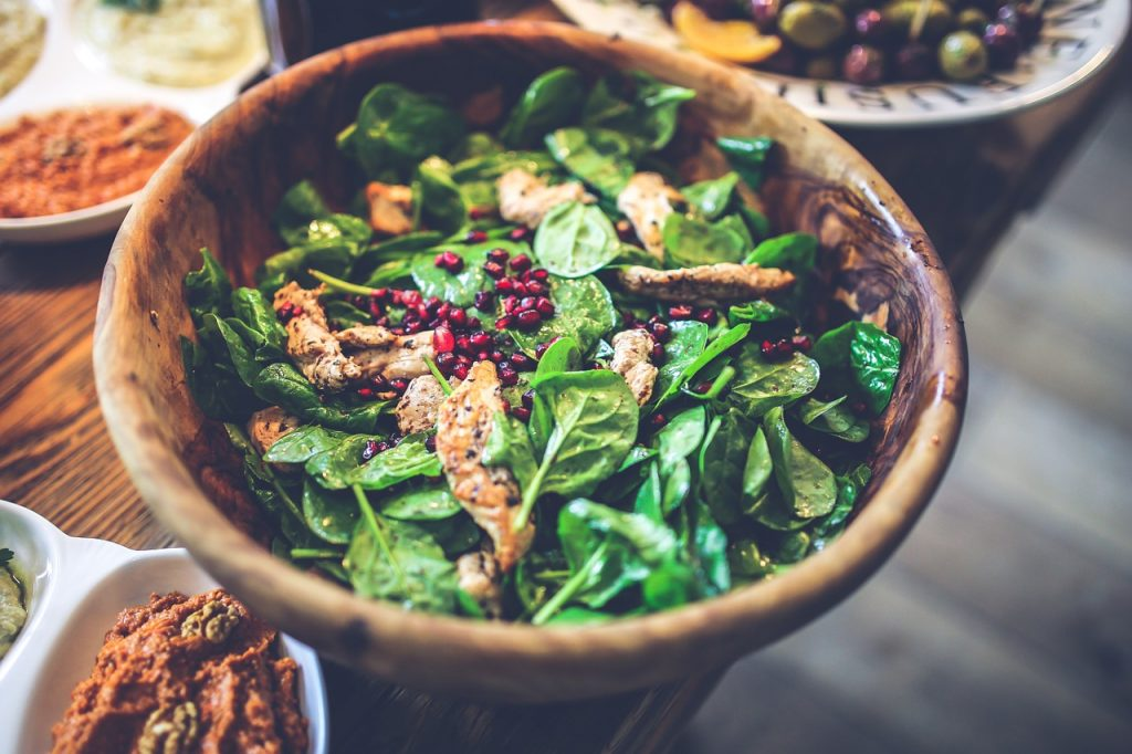 Ciotola di legno con l'insalata di spinaci crudi, pezzi di pollo arrostito, e chicchi di melagrana.