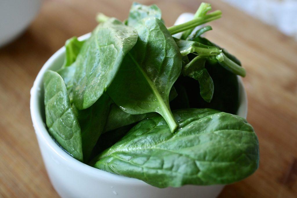 ciotola di ceramica bianca con foglie di spinaci crudi.