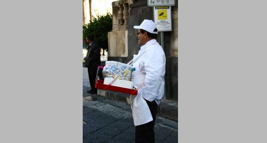 Venditore di bomboloni in giro per il centro storico catanese.