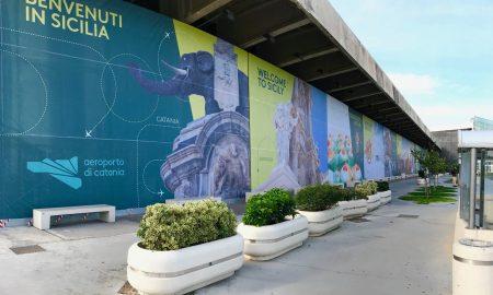 """Marciapiede dell'aeroporto di Catania con fioriere e cartellonistica nelle vetrate con i principali monumenti di Catania e la scritta """"Benvenuti in Sicilia"""""""