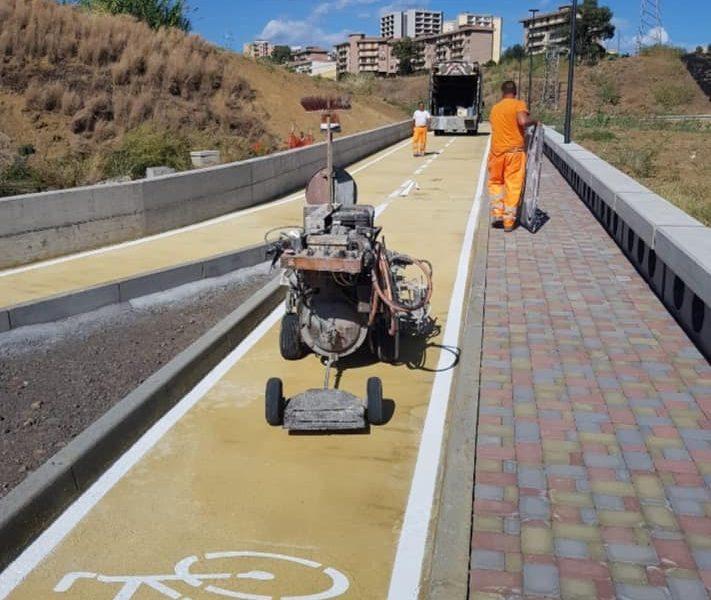 lavoratori impegnati nel rifinire la pista ciclabile a Librino