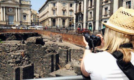 Turista di spalle che scatta una fotografia all'anfiteatro romano di Catania