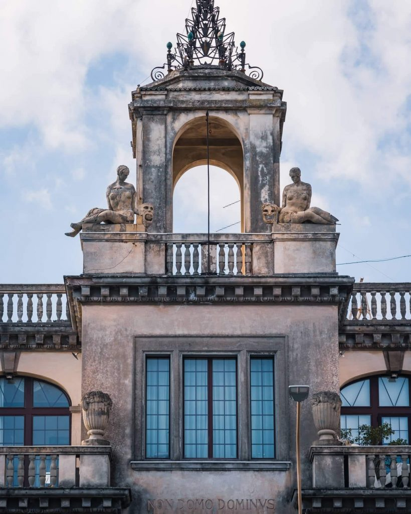 Dettagli della parte sommitale della facciata di Villa Iole Pantò, con le figure allegoriche poste ai lati, intente a sorreggere le maschere, chiaro riferimento all'arte di Angelo Musco, la cuspide in ferro battuto e l'iscrizione latina.