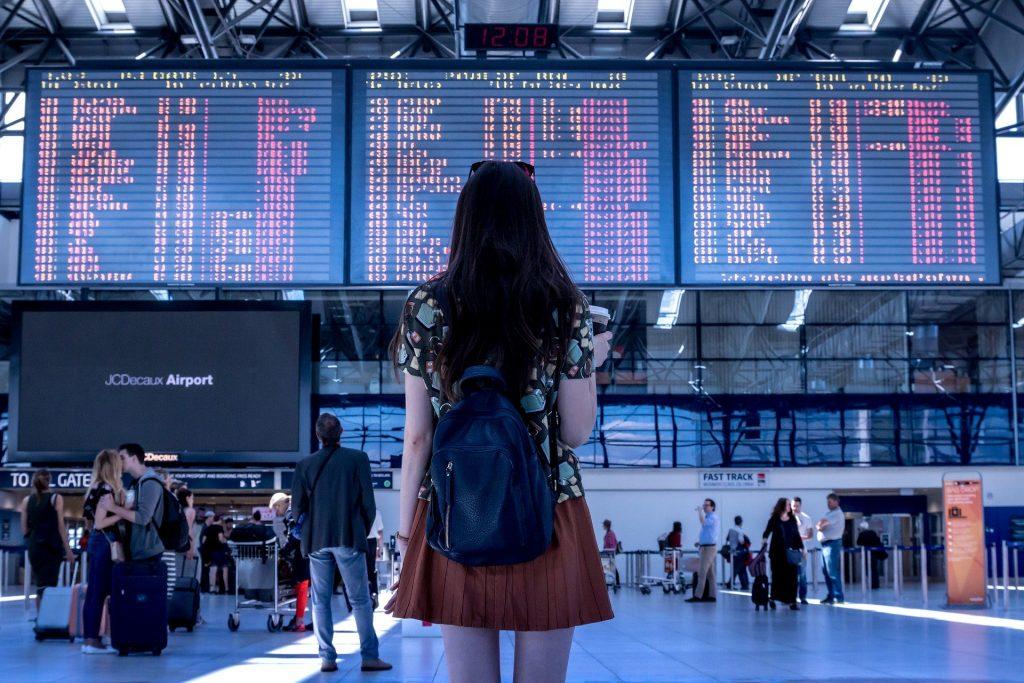 Viaggiatrice in primo piano, sullo sfondo tabelloni aerei - caro voli - Credit: Pixabay