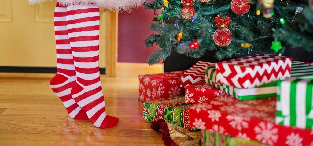 Regali di Natale in primo piano sotto un albero, con dei piedi con calze a righe di una donna che può essere la Vecchia di Natali del passato.