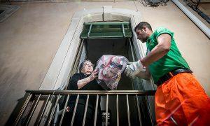 Raccolta differenziata - Donna consegna rifiuti ad addetto Dusty